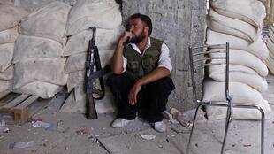 A member of the Free Syrian Army rests at a front line in the Hanano area of Aleppo city