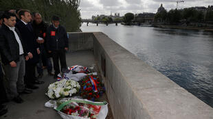 Emmanuel Macron (2ndL) stands next to Said Bouarram (L), son of Brahim Bouarram, as he pays hommage to Brahim Bouarram, a Moroccan who drowned in 1995 when right-wing extremists threw him from a bridge after a National Front rally