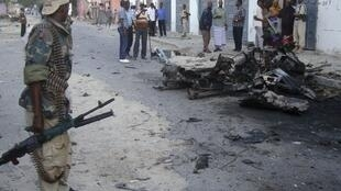 A Somali soldier stands at the scene of a suicide car bomb that exploded near Muna Hotel