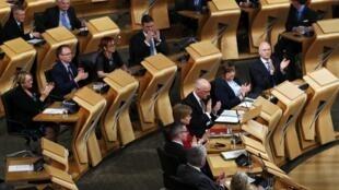 Deputados escoceses aplaudem a aprovação do segundo referendo separatista nesta terça-feira, 28 de março de 2017.