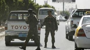 Police officers inspect vehicles on a street in Sanaa