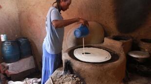 Une jeune éthiopienne prépare l'injera une galette faite à partir de farine de teff.