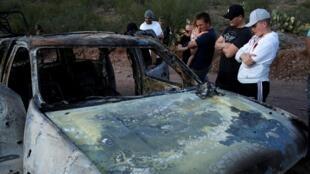 Des proches des neufs personnes assassinées près de la carcasse calcinée de la voiture des victimes, à Bavispe, dans l'État de Sonora, le 5 novembre 2019.