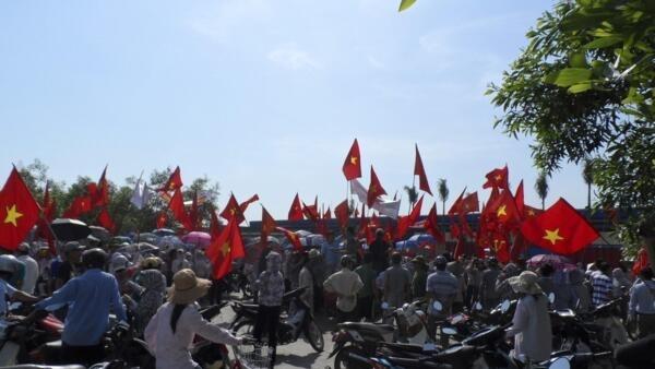 Trabalhadores agitam bandeiras vietnamitas durante manifestação antichinesa em uma fábrica de sapatos de propriedade chinesa  no norte do Vietnã nesta quarta-feira (14).