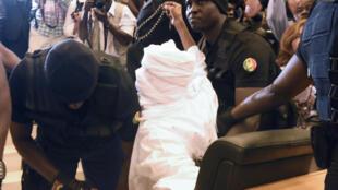 L'ancien président du Tchad Hissène Habré (de dos, au centre), est escorté lors du premier jour de son procès, le 20 juillet 2015 à Dakar.