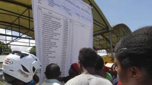 Indonésios olham a lista de passageiros do vôo