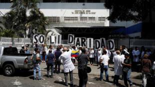 """Ciudadanos y médicos venezolanos sostiene un cartel de """"Solidaridad"""" frente a un hospital de niños público en Caracas durante el apagón, el 10 de marzo de 2019."""