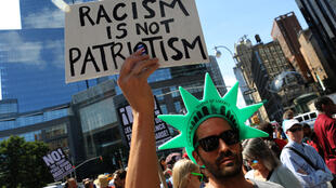 """A protester holds a sign reading """"Racism is not Patriotism"""" at a march against white nationalism in New York City, the day after the attack on counter-protesters at the """"Unite the Right"""" rally organized by white nationalists in Charlottesville, Virginia, U"""