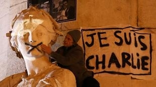 A man touches the spray-painted shut mouth of a statue during in a solidarity march in Paris on 11January 2015.