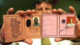 Août 1999: cet officier de la police belge montre les cartes d'identité des deux enfants. Fodé et Yaguine sont morts dans le train d'atterrissage d'un avion reliant Conakry à Bruxelles, le 2 août 1999.