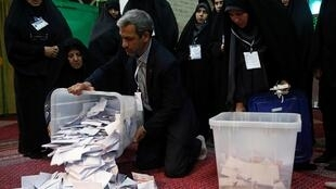 Iranian poll workers empty ballot boxes after the parliamentary election voting time ends in Tehran, 22 February 2020.