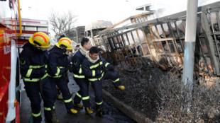 Bombeiros trabalham ao lado de carros incendiados nas proximidades da planta industrial química de Zhangjiakou, na província de Hebei, na China.
