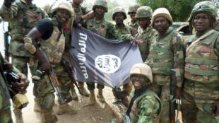 Des soldats nigérians posent devant le drapeau de Boko Haram après avoir démantelé un camp de la secte armée dans l'Etat du Yobe, en février dernier.