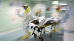 Miembros del servicio de emergencias médicas con riesgo biológico de la Comunidad de Madrid traslada a un paciente de coronavirus en la capital de España, una imagen divulgada el 9 de abril de 2020 por el Gobierno regional madrileño