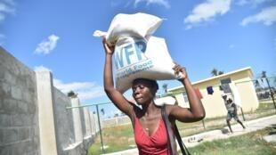 Vítimas do furacão Matthew recebem alimentos do Programa Mundial de Alimentos (PMA) na cidade de Tobeck, Les Cayes, Haiti. 13 de Outubro, de 2016.