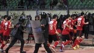 Riot police guard Al Ahli soccer players as they flee Port Said Stadium on 1 February