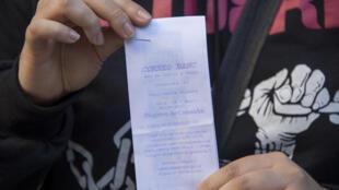 Una mujer muestra su comprobante de anotación en el registro de compradores de marihuana, el 2 de mayo de 2017 en Montevideo.