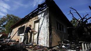 Un experto en explosivo examina una casa que recibió un proyectil en Timorin, al este de Ashod, Israel, el 21 de noviembre de 2012.