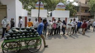 Des personnes font la queue pour recevoir du riz distribué gratuitement par le gouvernement, le 3 avril 2020.