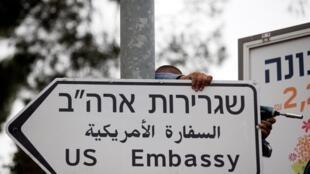 Un obrero colgando al aviso señalando la embajada de Estados Unidos, 7 mayo de 2018.