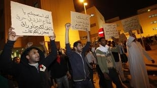 People hold signs as they protest for demonstrators who were injured in a police crackdown