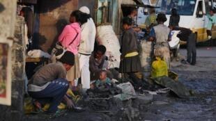 Dans le quartier populaire d'Anbohijatovo à Antananarivo, les vendeurs de charbon, noirs de suie, proposent leur marchandise au détail ou en sacs, selon le pouvoir d'achat du client, le 1er août 2019.