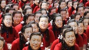 """习近平访问印度金奈与印度总理莫迪举行峰会,当地大学生戴着面具组成""""习近平""""三个大字热烈欢迎近景。"""