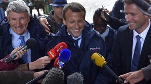 """French Economy Minister Emmanuel Macron (C) flanked by French """"Mouvement pour la France"""" (MPF) president, and creator of the Puy-du-Fou theme park Philippe De Villiers (L) and President of the Puy-du-Fou theme park Nicolas de Villiers (R), winks as he talk"""
