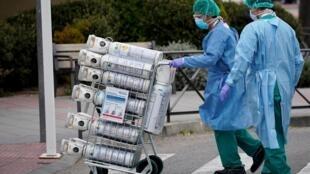 En Espagne, du personnel soignant réceptionne des bouteilles d'oxygène pour un hôpital de Madrid, le 30 mars 2020.