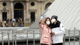 Um casal usando máscaras posa para uma selfie perto da Pirâmide do Louvre, em Paris, França, 5 de março de 2020.