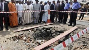 Президент Нигерии Гудлак Джонатан (в центре в черной шляпе) на месте взрыва, совершенного у католической церкви св. Терезы 31 декабря 2011 года