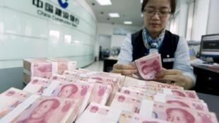 Yuanes chinos en una entidad financiera. China ha devaluado su valor esta semana consecutivamente