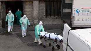 A health worker carries a body on a stretcher outside Gregorio Maranon hospital in Madrid