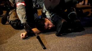 香港警察控制一名示威者,2019年10月14日。