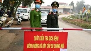Vietnamese police stand guard at a checkpoint set up at the Son Loi commune in Vinh Phuc province amid concerns about a COVID-19 coronavirus outbreak
