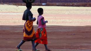 Mulheres caminham com capulanas coloridas.
