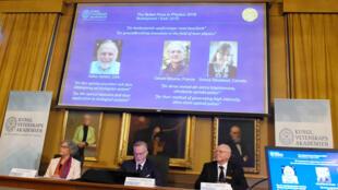 متس لارسون، عضو کمیتۀ نوبل در آکادمی سلطنتی علوم سوئد در استکهلم، برندگان جایزۀ نوبل فیزیک ٢٠١٨، آرتور اشکین از آمریکا، دونا استریکلند از کانادا و ژرار مورو از فرانسه، را اعلام میکند.