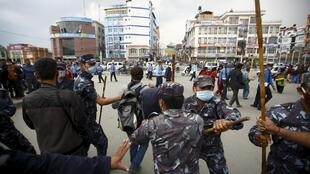 Nepalese police personnel try to stop earthquake victims from blocking traffic in a protest at the government's lack of aid provided to the victims in Kathmandu