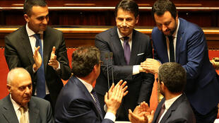 Novo primeiro-ministro italiano Giuseppe Conte recebe aplausos durante sua primeira sessão no Senado em Roma, ao lado dos vices Luigi di Maio (M5E) e Matteo Salvini da Liga (extrema direita), 5 de junho de 2018