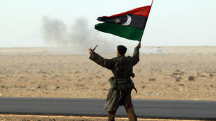 A rebel soldier waves the Libyan flag at Ras Lanouf on Friday