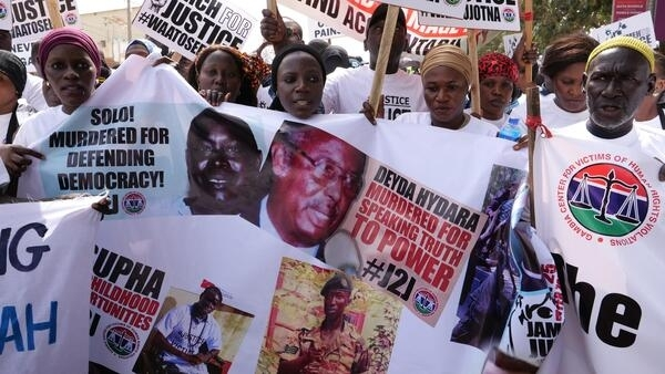 Protesters hold banners bearing the faces of victims of the regime of former Gambian dictator Yahya Jammeh, during a demonstration calling for Jammeh to be brought to justice in Banjul, 25 January, 2020.