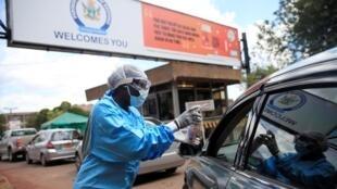 Un agent de santé dépiste et désinfecte les visiteurs pour empêcher la propagation du Covid-19 à l'extérieur d'un hôpital de Harare au Zimbabwe, le 26 mars 2020.