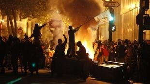 A demonstrator waves a flag as rubbish burns at the Occupy Oakland demonstration in Oakland, California
