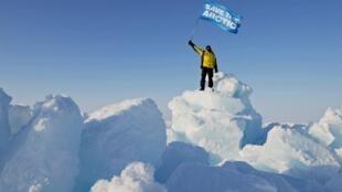 Một nhà hoạt động Greenpeace giơ cao lá cờ mang dòng chữ « Hãy cứu Bắc Cực ».
