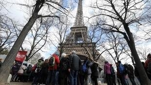 Tourists and visitors queue to pass the security check at the entrance to the new glass fence around the Eiffel tower in Paris on March 21, 2018.