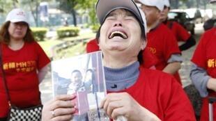 A mãe de um dos passageiros do voo MH370 mostra a foto do seu neto, que também morreu.