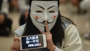 Une manifestante portant un masque, tient un téléphone portable avec des slogans «Cinq demandes, pas un repos», alors qu'elle assiste à un rassemblement en faveur de la démocratie dans un centre commercial du quartier de Yuen Long à Hong Kong le 21/11/19.