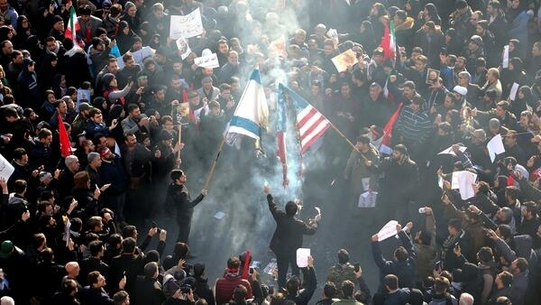 Iranians set a US and an Israeli flag on fire during a funeral procession organised to mourn the slain military commander Qasem Soleimani, Iraqi paramilitary chief Abu Mahdi al-Muhandis and other victims of a US attack in Tehran on January 6, 2020