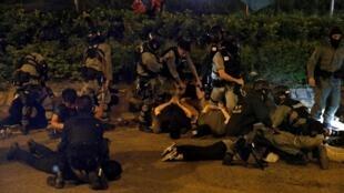 19日晚,港警抓捕企图离开理大的示威者。