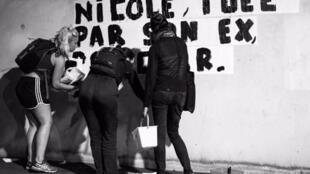 """Mujeres activistas pegando afiches contra las violencias de género en París, Octubre 2019: """"Nicole asesinada por su ex""""."""